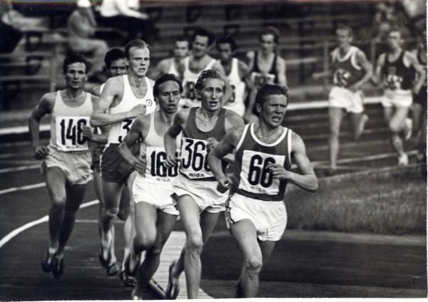 Starptautiskās sacensības vieglatlētikā «Rīgas Kausi» – sporta biedrības «Daugava» centrālais stadions. Grustiņš ir ceturtais skrējējs; Genādijs Hlistovs – otrais. 1970. gadu sākums. Autors nezināms. Foto no LSM krājuma (LSM 1139)