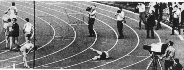 Juris Grustiņš nokrīt uz skrejceliņa pēc finiša PSRS Tautu 5. spartakiādes 5000 m skrējienā. Lai gan grūti saskatāms, Juris ar savu roku ir parakstījies un atzīmējis finiša laiku «13:34.2», kas joprojām ir Latvijas rekords. Autors: J. Kalniņš. Fotogrāfija publicēta žurnālā «Zvaigzne» 1971. gada septembra numurā